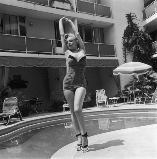 American actress Marilyn Monroe (1926 - 1962) stands next to a swimming pool in a strapless swimsuit and high heels, circa 1951.